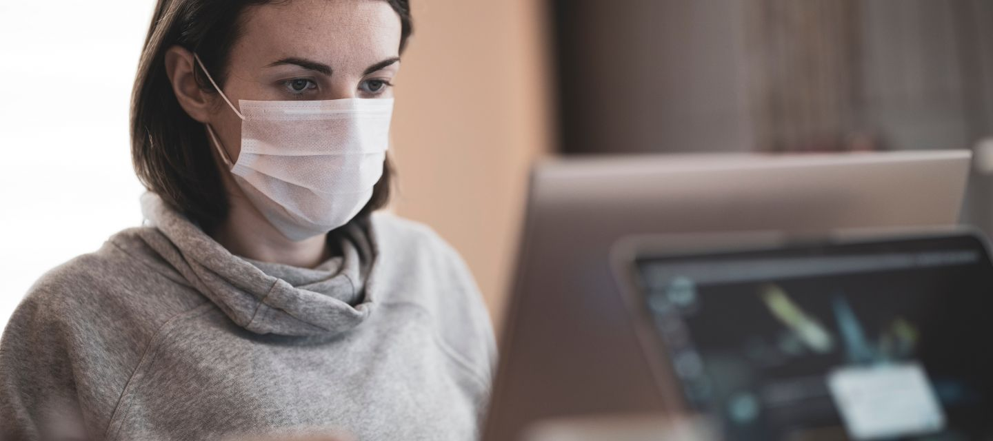 Woman wearing mask at a computer